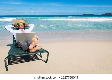 Barefoot businessman kicking back in a beach chair with laptop on his lap and sunglasses and straw hat on his head