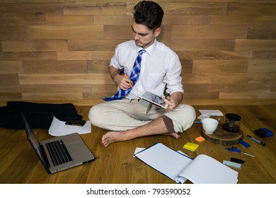 A barefoot businessman sits on the floor against a wall and using a laptop for read important news. Remote working, thinking about a solution. Young man working at home in funny clothes.