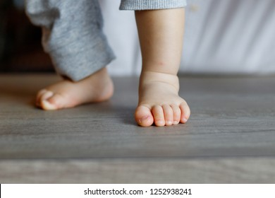 Barefoot child standing on the wooden table. The first steps in close-up. Healthy baby feet