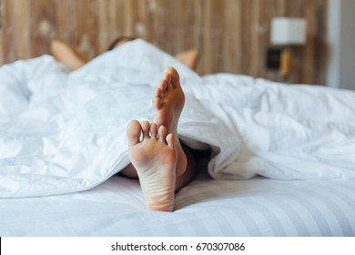 Barefoot chilling on bed, Chilling concept at hotel room, focus on foot soles
