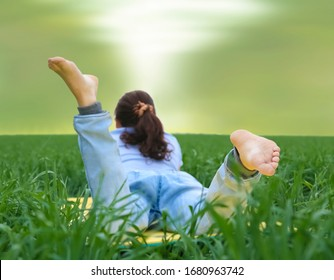 barefoot curly redhead woman lying in fresh green grass reading a book.A back picture of a woman lying on spring meadow. summer time season. unrecognizable person. young wheat field.