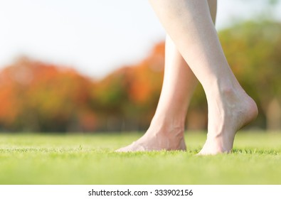 Barefoot feet walking on grass