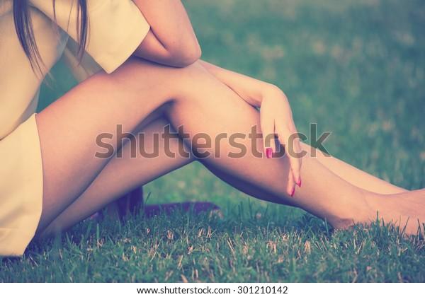 草のレトロな色合いの裸足の女性の脚