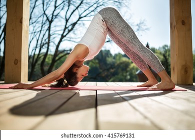 Barefoot Girl Is Engaged In Yoga On The Wooden Terrace On The Nature  Background. She