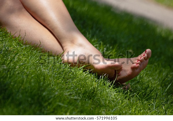 Barefoot girl on grass copyspace angle view