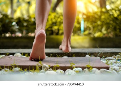barefoot girl walking on the stone floor in outdoor with sunlight
