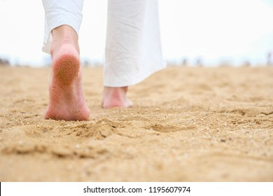 barefoot girl walking relax on the beach in good morning time with blur people in play sea