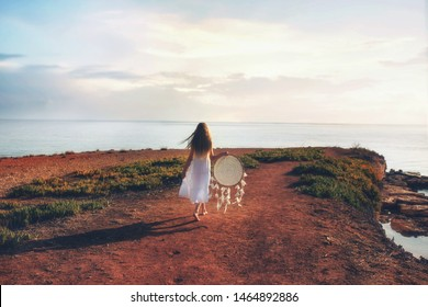 Barefoot girl is walking in white dress with dream catcher.