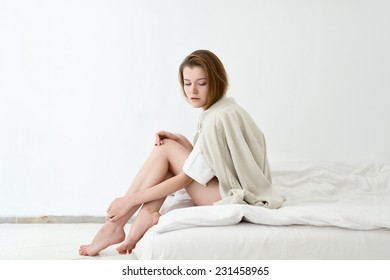 Barefoot girl in a white room sitting on the bed