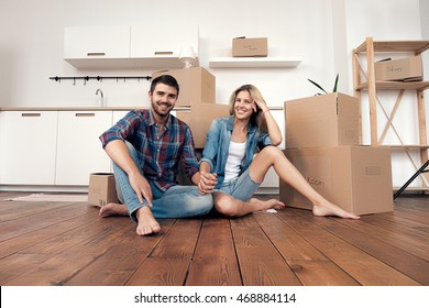 Barefoot happy couple holding hands in kitchen while moving in new home