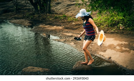 Barefoot happy indian woman in sunhat using stepping stones to cross the river.