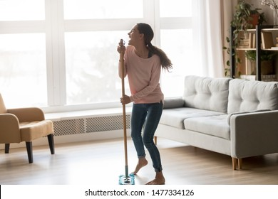 Barefoot happy young multiracial girl having fun during living room cleaning, using microfiber wet mop pad as microphone stand, dancing and singing, enjoying cleaning homework routine.