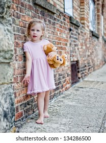 Barefoot little girl wearing pink dress and holding teddy bear standing on sidewalk next to brick wall