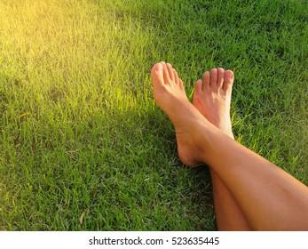 Barefoot lying on green grass.