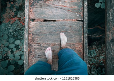 Barefoot man crossing old damaged wooden narrow bridge in the forest.
