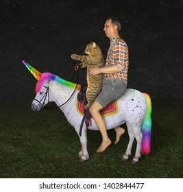 The barefoot man with his cat  is riding together on the real unicorn on the field at night.