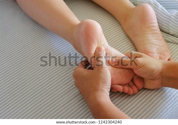 The barefoot massages for a girl in bed with a blue blanket in the morning make for a relaxing and fulfilling life for the couple.