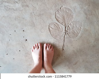 Barefoot on artistic rustic grey concrete floor with leaf pattern imprinted.