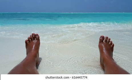 Barefoot on the white sand beach with blue waves background