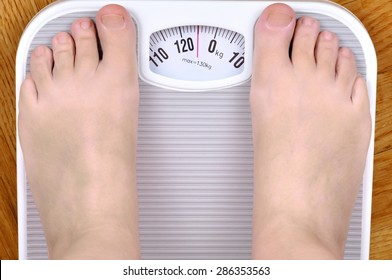 Barefoot overweight person standing on the scale