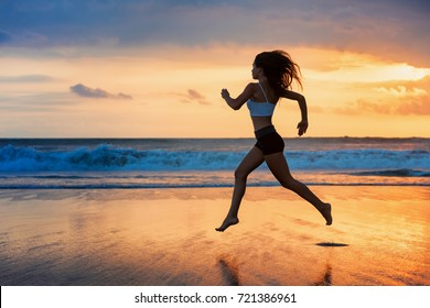 Barefoot sporty girl silhouette running along ocean surf by water pool to keep fit and health. Sunset black beach background with sun. Woman fitness, jogging sport activity on summer family holiday.