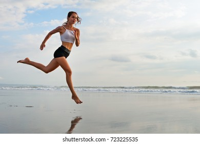 Barefoot sporty girl with slim body running along sea surf by water pool to keep fit and health. Beach background with blue sky. Woman fitness, jogging sports activity on summer family vacation.