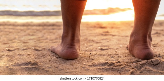 Barefoot standing on sand beach. two feet standing at the seashore with sea wave and sunset background. Bottom view from behind. Space for text or product object.