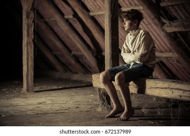 Barefoot teenage boy immobilized in a straight jacket sitting on a wooden beam covered in cobwebs in a shadowy attic in a conceptual atmospheric image with copy space