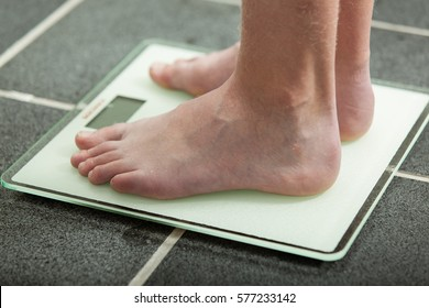 Barefoot teenage boy or young man weighing himself on a bathroom scale on a tiled floor with a close up side view of his feet