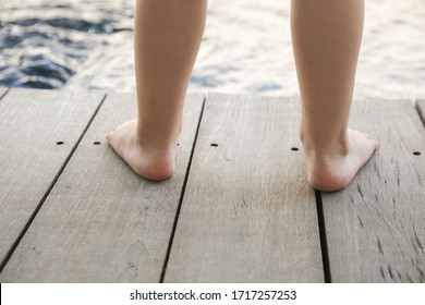 Barefoot toddlers feet standing on the wooden floor