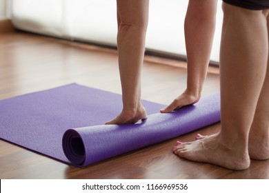 Barefoot woman folding purple yoga mat in studio. Female student rolling equipment after morning practice. Pilates, workout, healthy lifestyle, exercise, flexibility concepts