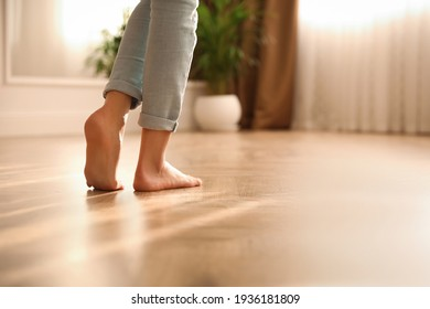 Barefoot woman at home, closeup. Floor heating system