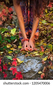 barefoot  woman legs and hands in yoga stretch pose in colorful autumn leaves outdoor day shot