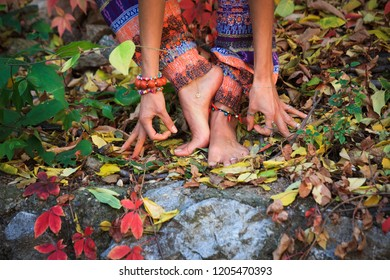 barefoot  woman legs and hands in yoga and mudra gesture in colorful autumn leaves outdoor day shot