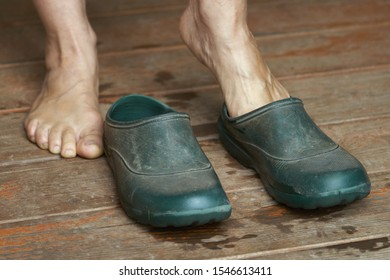 Barefoot woman puts rubber boots on standing on a wooden floor of a country house