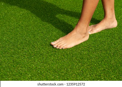 Barefoot Woman steps on Green Artificial grass. Female without shoes walks on soft artificial turf.