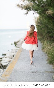 Barefoot woman taking a relaxing walk at the sea walking away from the camera along a walkway above the ocean