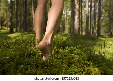 Barefoot woman walking in forest