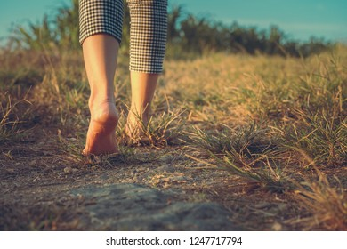 barefoot woman walking on the ground with sunset light in the countryside