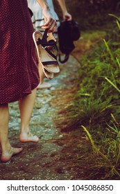The barefoot women in dresses with shoes in hands. Rear view