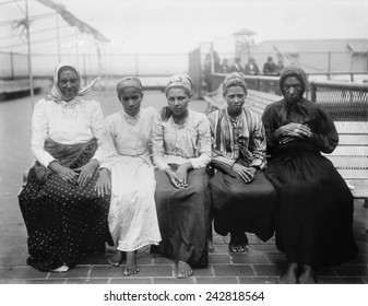 Barefoot women immigrants at Ellis Island are from the Caribbean. Ca. 1910.