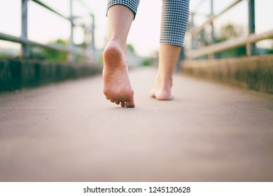 barefoot women walk on the ground cement bridge with evening time in the countryside