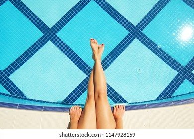 Barefoot young woman with clean shaved feet, red pedicure. Female sitting on edge legs over pool. Blue white tiles of poolside by luxurious hotel spa center. Background, copy space, top view, close up