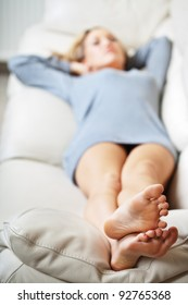 Barefoot young woman lying on sofa, shallow depth of field, focus on foot soles