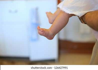 barefooted baby in father's arms