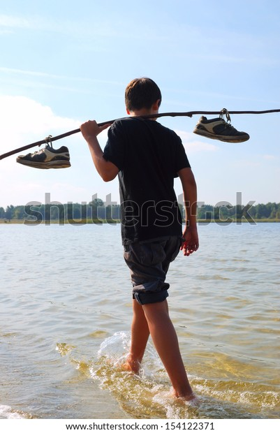 Barefooted boy is walking along a river bank. Dark silhouette is photographed against the river, forest and the sky. Teenage boy is carrying a stick with shoes on his shoulders.