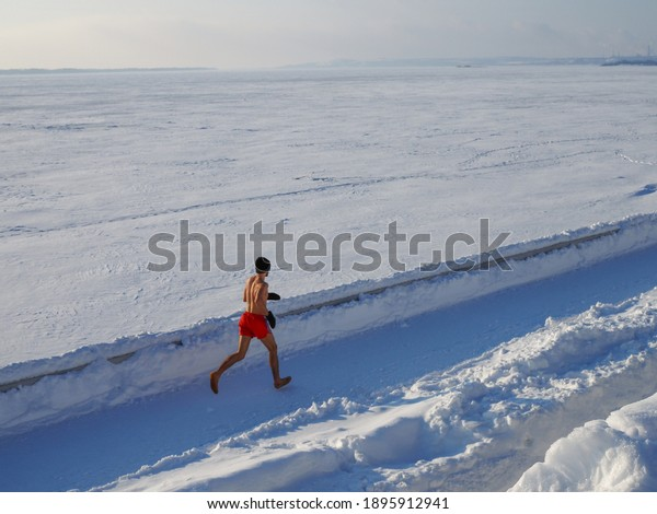 Barefooted man with a naked torso engaged cold conditioning on ice of a frozen river.