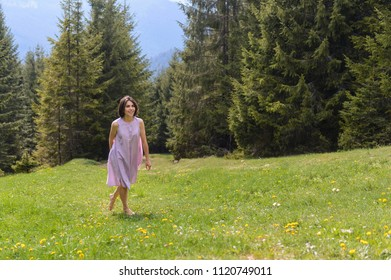 barefooted woman walking on grass at pine forest