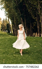 barefooted young fair-haired bride walking along the grass in an exotic park, in a long white dress, a walk after the wedding ceremony, a wedding ceremony