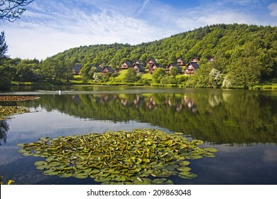 Barend Holiday Village reflected in Barend Loch with Water Lillies in foreground. Taken at Barend, Dumfries and Galloway, Scotland, UK.